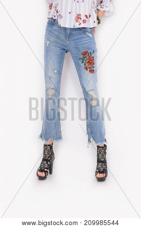 Woman legs in embroidered flowers jeans and black high heels shoes posing in studio