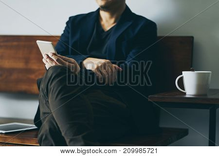 Businessman sit on wooden chair with coffee and using smartphone selective focusing .