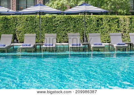 Outdoor swimming pool with umbrella and daybeds