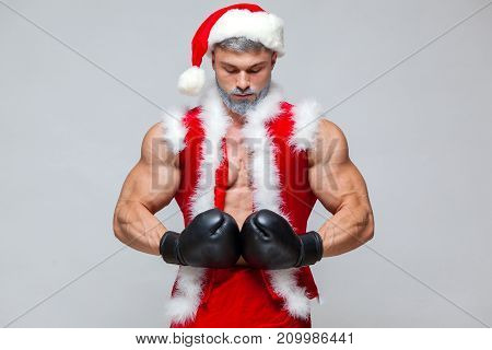 Sport, activity. Sexy Santa Claus with boxing glove. Young muscular man wearing Santa Claus hat demonstrate his muscles. on a homogeneous gray background.