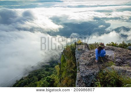 Happy woman sitting on a cliff side