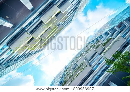 Low angle perspective view of modern office building with green eco concept balcony .
