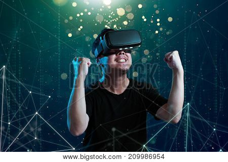 Asian man wearing virtual reality goggles in cyberspace imaging.