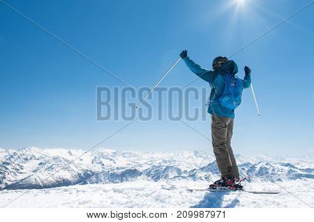 Happy skier at the top of mountain raising arms at sky for goal achieved with copy space. Back view of joyful man with raised hands looking at a panoramic view of the snow white mountain landscape.