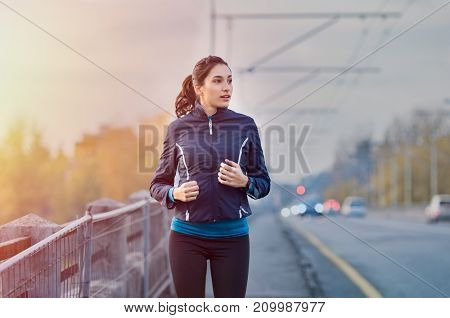 Young woman jogging on the street early in morning. Fit and healthy brunette girl working out during winter in the city. Runner work out in an urban context on bridge.