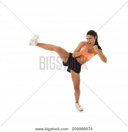 young attractive and furious latin sport woman in fight and kick boxing training workout throwing aggressive kick attack isolated on white background in gym exercise and personal defense concept