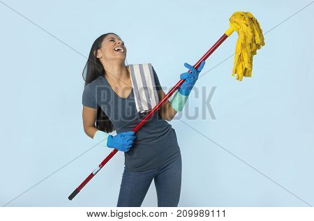 young attractive happy Latin woman in washing gloves holding mop having fun singing and playing air guitar excited and cheerful isolated on blue background in house cleaning and domestic work concept