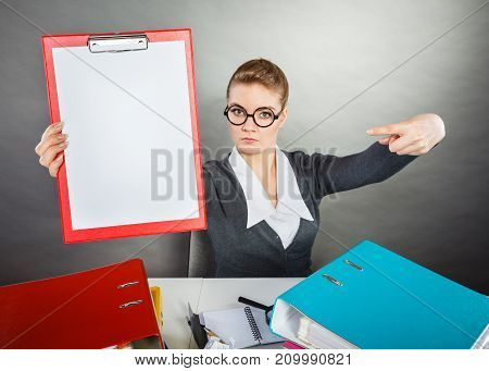 Office nerdy job work documentation concept. Smiling woman pointing at binder. Young female gesturing at documents.