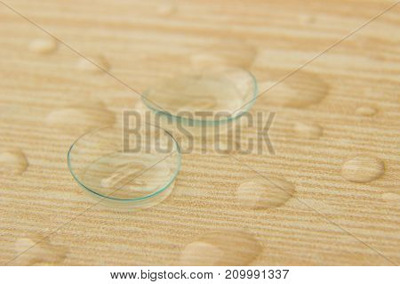 Contact lenses for eyes close-up with drops of solution on a wooden table