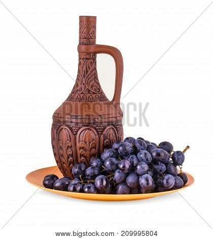 clay bottle and grapes on a white background