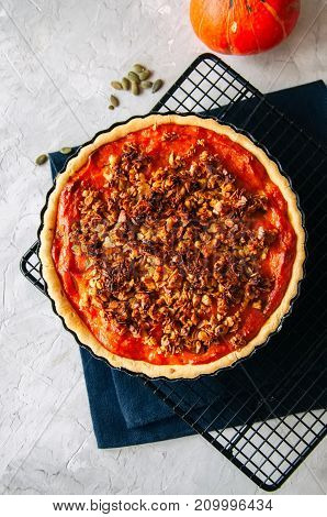 Pumpkin pie with oat pecan crust on a white stone background - traditional american baking