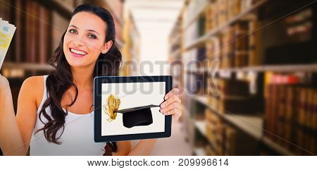 Pretty brunette using tablet pc against close up of a bookshelf