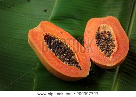Papaya fruit on wooden background.Slices of sweet papaya on banana leaves background.