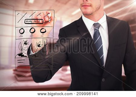 Businessman writing with a marker against digital image of workplace