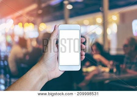 Man's hand shows mobile smartphone with white screen in vertical position Blurred or Defocus image of Restaurant or Cafeteria for use as Background vintage tone. - mockup template and clipping path