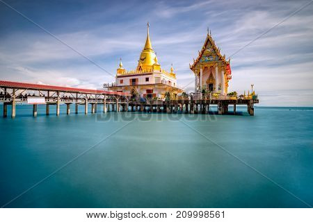 Beautiful scene of thai temple at Wat Hong Thong temple at Chachoengsao province Thailand. It's popular thai temple in Thailand. Buddhist church and gold pagoda in the sea.