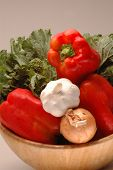 broccoli rabe, garlic, yellow onions and red bell peppers in salad bowl poster