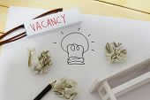 Vacancy and employment concept. White paper with drawing of a light bulb crumpled papers glasses pencil mini toy table and word VACANCY written on a small piece of paper. poster