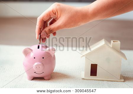 Woman Hand is Putting a Money Coin into Piggy Bank for Savings on The Bedroom., Female Hand is Inserting Coin in Pink Piggybank., Saving for Finance Future, Business Banking and Financial Real Estate