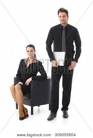 Businessman and businesswoman over white background, looking at camera, smiling.