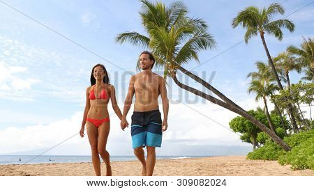 Couple walking on beach. Young happy interracial couple walking on beach smiling holding hands in swimsuits. Asian woman, Caucasian man.