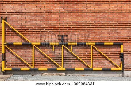 A Brown Brick Wall And A Wing Of A Gate At It.