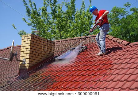 House Roof Cleaning With Pressure Tool. Worker On Top Of Building Washing Tile With Professional Equ