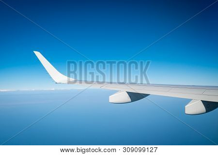 Wing Of Plane Over White Clouds. Airplane Flying On Blue Sky. Scenic View From Airplane Window. Comm