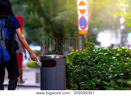 Woman Hand Throwing Twisted Empty Water Bottle In Recycle Bin. Gray Plastic Recycle Bin. Backpacker