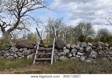 Traditional Wooden Stile Crossing An Old Dry Stone Wall At The Swedish Island Oland