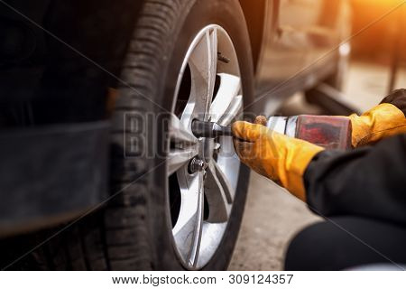 Auto Mechanic Man With Electric Screwdriver Changing Tire Outside. Car Service. Hands Replace Tires
