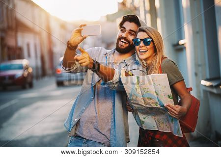 Summer Holidays, Dating And Tourism Concept. Smiling Happy Couple With Map In The City