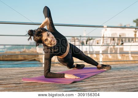 Pretty Brunette Young Woman With White Wireless Headphones In A Black Jumpsuit Takes Plank Workout O