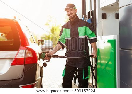 Bearded Guy In Green And Black Uniform Smiling And Looking At Camera While Filling Modern Vehicle Wi