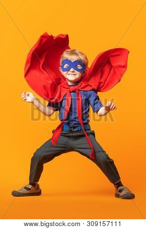 A full length portrait of a funny happy young boy posing in the costume of superhero. Kids development and education concept.