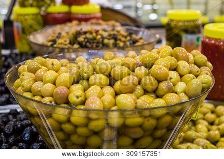 Close Up Of Delicious Organic Green Olives In Bowl For Sale In Supermarket.
