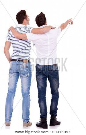 Back view of  two young men pointing at something. Rear view. Isolated over white background.