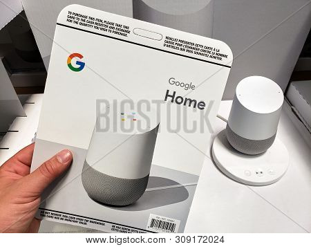 Montreal, Canada - June 20, 2019: A Hand Holding Costco Cacardboard Selling Card With Google Home. G