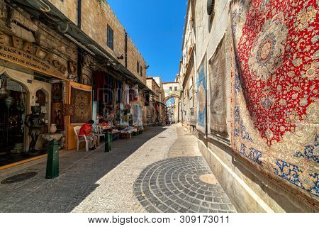 JERUSALEM, ISRAEL - JULY 16, 2018: Traditional shops and carpets on the wall on via Dolorosa - famous street in Old City of Jerusalem where Jesus walked on the way to  his crucifixion.