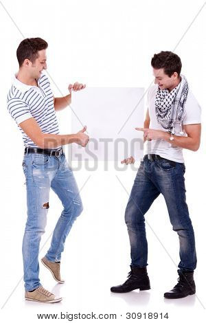 two young men holding a blank board on white background, one pointing to it and one gesturing ok with thumbs up