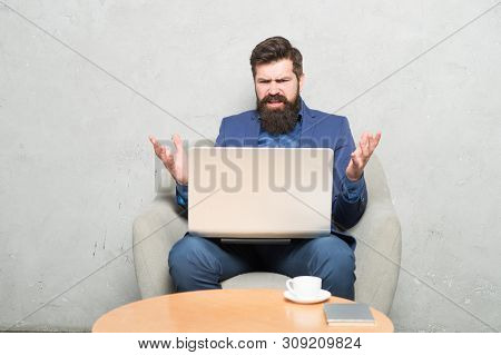 Having Some Problems At Work. Hipster Drinking Coffee And Working On Computer Work Station. Bearded