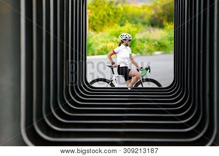 Young Woman Cyclist Resting with Road Bicycle near Urban Constructions in the City. Healthy Lifestyle and Urban Sport Concept.