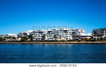 Large Waterside Houses Built In Front Of Condominium Apartments With Riverside Grass Frontage, Stone