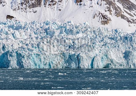 Blue glacier in Kongsfjorden fjord in Svalbard, a Norwegian archipelago between mainland Norway and the North Pole