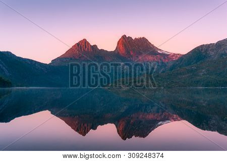 Mountain Landscape At Sunrise. Sunlit Mountain Peaks Reflected In The Lake, Nature Background. Cradl