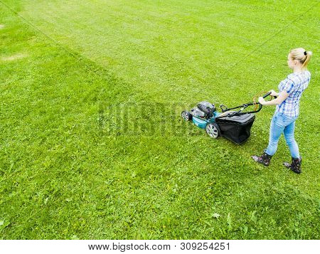 Beautiful Girl Cuts The Lawn. Mowing Lawns. Aerial View Beautiful Woman Lawn Mower On Green Grass. M