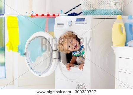 Child In Laundry Room With Washing Machine Or Tumble Dryer. Kid Helping With Family Chores. Modern H
