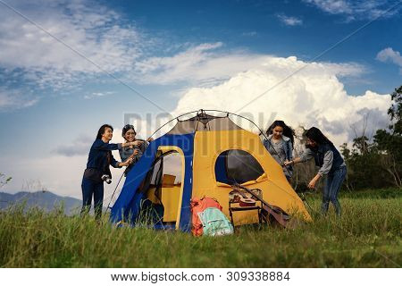 Group Of Women Helping Build A Tent For Resting In The Camp.camping Vacation Time On Weekend.