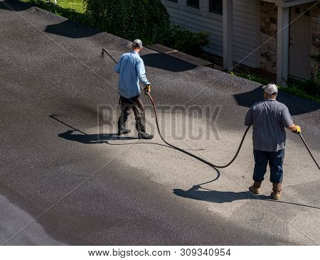 Workers Applying Blacktop Sealer To Asphalt Street Using A Spray To Provide A Protective Coat Agains