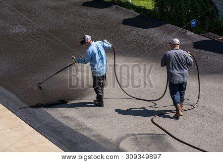 Morgantown, West Virginia - 3 June 2019: Workers Applying Blacktop Sealer To Asphalt Street Using A
